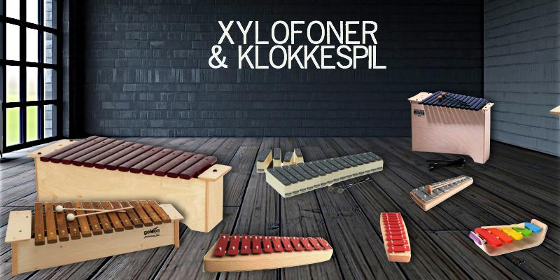 Et udvalg af xylofoner og klokkespil i forskellige størrelser, nogle i træ og nogle i metal.
