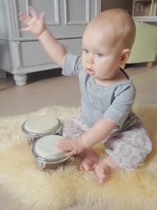 baby alma på 6 mdr. sidder på gulvet og trommer på sin baby bongo