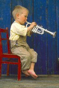 Lille dreng spiller på en legetøjstrompet i sølvlook med fire lydknapper
