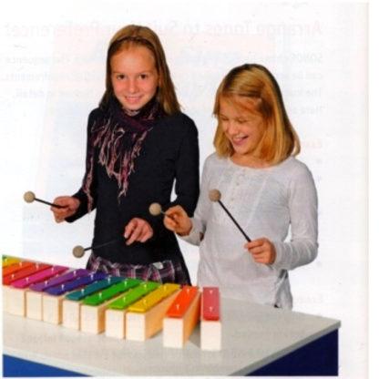 to børn spiller på store enkeltstående klangstave metallofoner med to køller hver