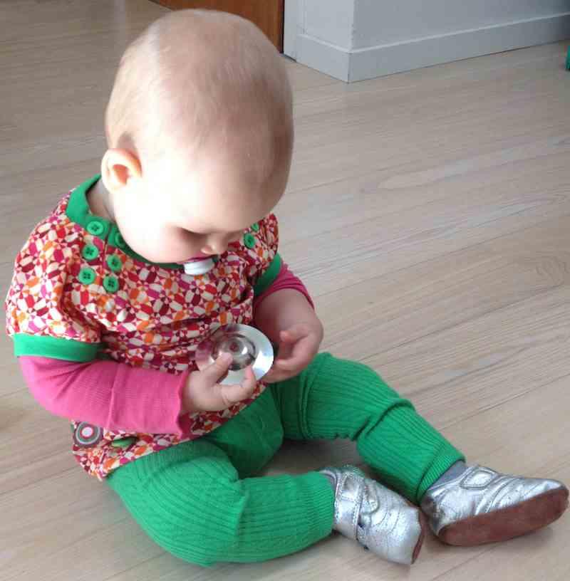 Lille alma sidder og leger med et fingerbækken