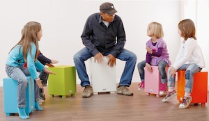 4 børn og en musiklærer sidder på hver sin cajon og trommer
