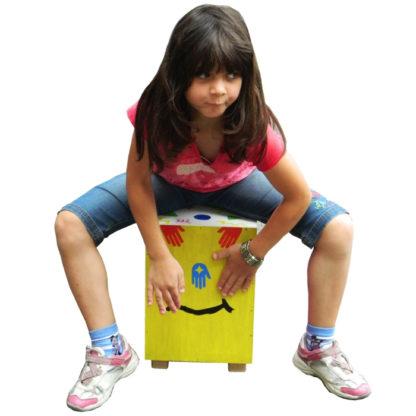 junior pige spiller på sin hjemmelavede cajon tromme