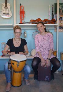 To kvinder spiller tromme i musikbutik