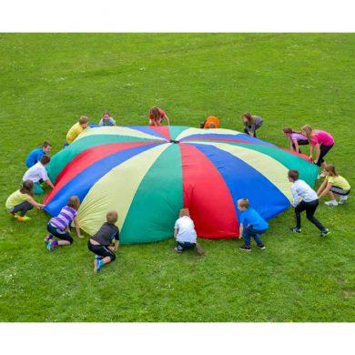 En flok børn leger udendørs med en stor faldskærm