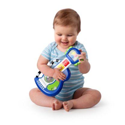 en lille dreng sidder og leger med sin rock guitar