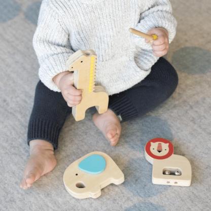 Lille barn leger musikleg med 3 musikalske jungledyr