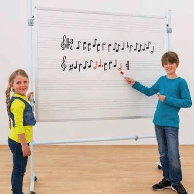 To børn står foran en tavle med noder
