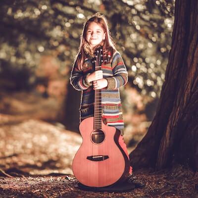 En pige holder en akustisk guitar