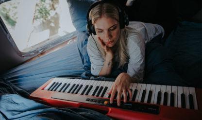 en kvinde spiller på keyboard med hovedtelefoner på